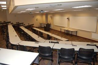 Lecture hall with two large whiteboards and multiple tiers of seating